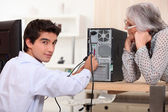 Young man trying to repair computer — Stockfoto