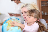 Housewife with child and globe — Stock Photo
