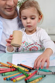 Father and daughter coloring in with crayons — Stock Photo