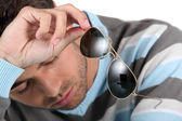 Tired man holding sunglasses — Stock Photo