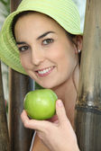 Woman stood by wooden poles holding a green apple — Stock Photo