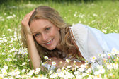 Woman lying in a grassy field — Foto de Stock