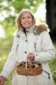 A mature woman holding a mushroom basket — Stock Photo