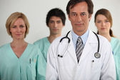 A doctor and three nurses behind him, all looking at us. — Stock Photo