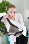 Young woman using an exercise machine — Stock Photo