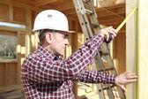 Carpenter measuring a door frame — Stock Photo