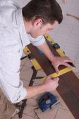 Man measuring wood flooring — Stockfoto