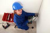 Een vrouwelijke elektricien op het werk. — Stockfoto