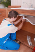 Fontanero arreglar una tubería — Foto de Stock