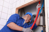 Plumber feeding flexible pipes behind a tiled wall — Stock Photo