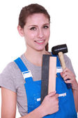 Female labourer holding mallet and sand paper — Stock Photo