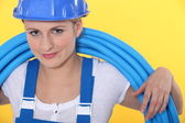 A tradeswoman with tubes coiled around her neck — Stock Photo