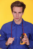 Elettricista tenendo un multimetro intorno al collo — Foto Stock