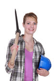Young female bricklayer posing with pickaxe and hard hat — Stok fotoğraf