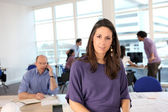 Woman fronting a busy office — Stock Photo
