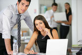 Couple flirting at work — Stockfoto