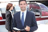 Man in pak het maken van notities voor een vliegtuig — Stockfoto