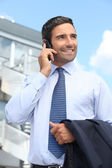 Businessman speaking on a cellphone outside an office building — Stock Photo
