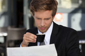 Businessman reading documents and drinking expresso — Stock Photo