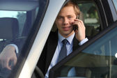 Junior executive on the phone driving luxury car — Stock Photo