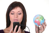 Woman charging battery of cell phone with globe — Stock Photo