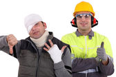 Healthy construction worker standing next to an injured man — Stock Photo