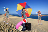 Photo-montage of funny girl with parasol at the beach — Stock Photo