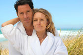 Couple in robes on the beach — Stock Photo