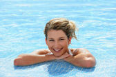 Happy blond girl at a poolside — Stock Photo