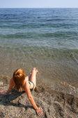 Mujer joven puesto en la arena — Foto de Stock