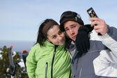 Giovane coppia con un cameraphone su una pista da sci — Foto Stock