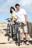Couple taking their bikes to the beach — Stock Photo