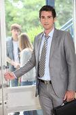 Teacher carrying briefcase opening door — Stock Photo