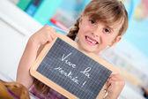 Petite fille écrit sur le tableau noir — Photo