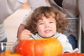 A plump kid carving a pumpkin. — Stock Photo