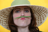 Woman balancing a green bean between her lips and her nose — Stock Photo