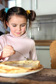 Little girl eating pancakes in kitchen — Stock Photo