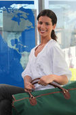 Young woman smiling with travel bag — Stock Photo