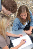 Three young , one of them writing in a binder on her lap. — Stock Photo