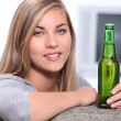 Teenager with a bottle of beer - Stock Photo