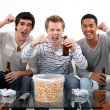 Stock Photo: Buddies watching football match on telly