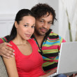 Couple at home using a laptop computer - Stock Photo