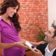 Woman offering man a small gift — Stock Photo #8482483