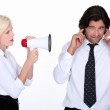 Woman talking through a megaphone and a man plugging his ears — Stock Photo