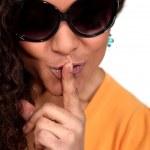 Woman wearing sunglasses making shush gesture — Stock Photo