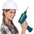 Foto Stock: Smiling tradeswomholding power tool