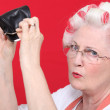 Grandma with hair curlers and empty purse — Stock Photo