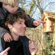 Father and son looking at a birdbox - Foto de Stock