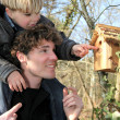Father and son looking at a birdbox - Foto Stock