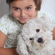 Young girl holding small white dog — Stock Photo #8485263
